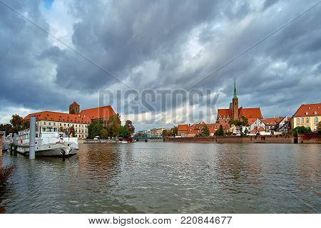 Wroclaw Old Town. Cathedral Island (Ostrow Tumski) is the oldest part of the city at the sunset. Cathedral of St. John and Blessed Virgin Mary Church on Island Piasek and Odra (Oder) river Tumski bridge (Tumski Most)