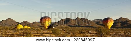 A panoramic photo of some hot air balloons preparing to lift off on a cool Arizona morning.