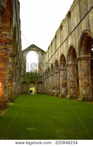 Fountains Abbey, Ripon, North Yorkshire, England, UK - December 27, 2016 : The historical 13th century Fountains Abby Interior of the abbey church looking down the nave