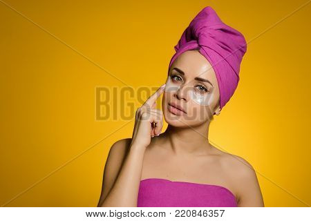 attractive young girl with a pink towel on her head pasted patches under the eyes