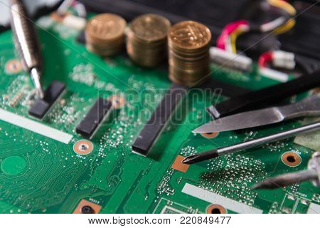 PCB green with tools and coins, a screwdriver, a soldering iron, knife, close up. components on the motherboard of the laptop.