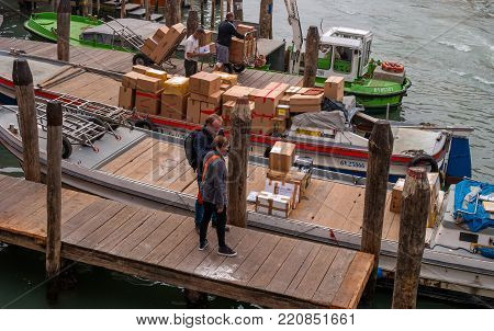 Venice, Italy - October 13, 2017: pier on the Grand Canal. Designed for cargo ships. cargo ships. Boats and gondolas are moored. Tourists visiting the pier. There is unloading of the cargo boat.
