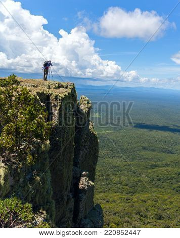 Wildlife photographer on mountain summit taking pictures of sunset in landscape and blue sky. Stock photo