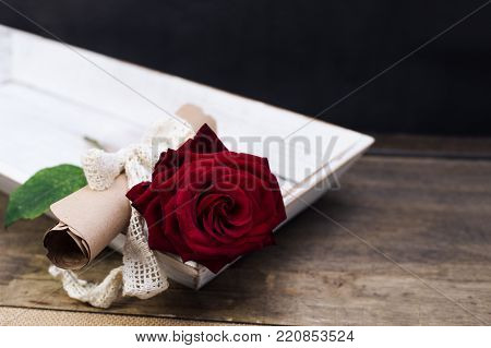 surprise for St. Valentine's Day on a table: red rose and a message on papyrus vintage paper with a ribbon.