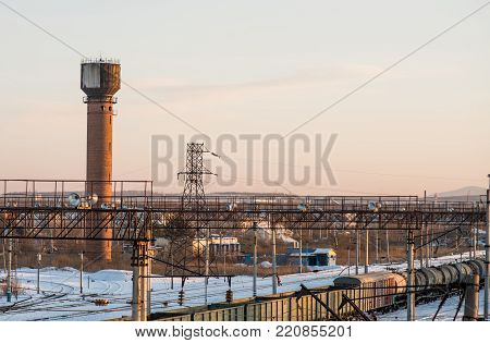 industrial area. railways with trains and brick tower in the background