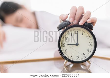 Close Up Alarm Clock. Happy Woman Being Drowsy On Bed After Waking Up In The Early Morning At Window