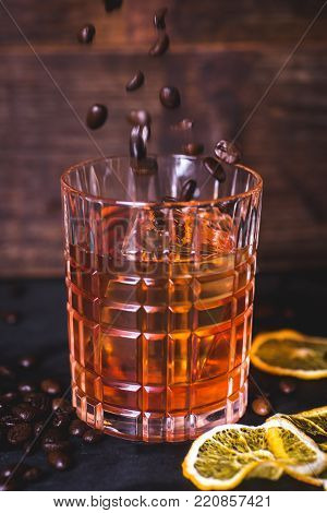 Grains of coffee fall into a glass with a drink. A glass with whiskey on a wooden background. Close-up of alcohol in a glass. Whiskey or bourbon is poured into a glass. Dried lemon slices and coffee grains lie on the table.