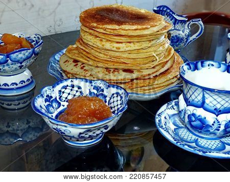 Traditional russian blini (pancakes) on the dishe Gzhel style. Maslenitsa is an Eastern Slavic traditional holiday. Gzhel-Russian folk craft of ceramics and production porcelain and a kind of Russian folk painting