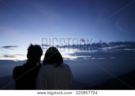 The lover are standing to seeing sunrise on the mountain , lover are seeing beautiful blue sky in the morning with concept valentine day .