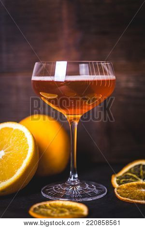 Oranges are reflected on the glass of a glass with a drink. Close-up of a glass with a drink and foam. Dried orange slices are on the table. A glass with a drink and a sheet of mint. Cut orange in the background.