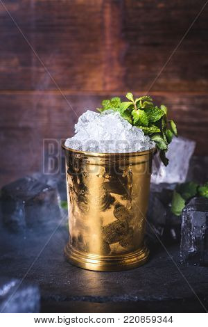 A tin can with ice is decorated with a sprig of mint. Light smoke envelops the bucket.