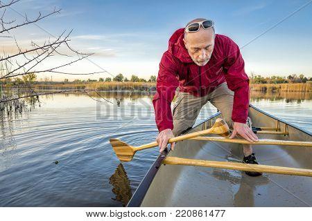 senior paddler boarding  a canoe on a calm lake, Riverbend Ponds Natural Area, Fort Collins, Colorado