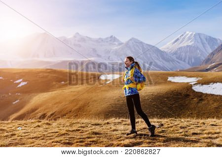 active sports girl in a blue jacket travels along the Caucasian ridge with a backpack and tent