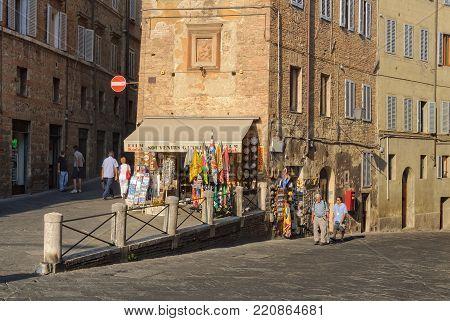 Tourists at the sunlit corner of Via della Sapienza and Via del Paradiso - Siena, Italy, 23 September 2011