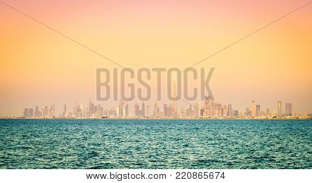 Seaside view of skyline of Dubai's downtown at sunset