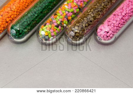 Plastic pellets .Polymeric dye in test tubes on gray background. Plastic raw for industry