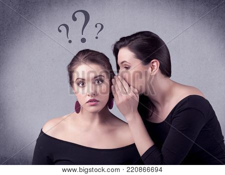 A teenager girl looking confused with drawn question marks above the head, while a girlfriend whispers something in her ear concept.