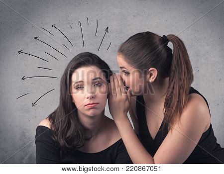 A cute teen caucasian girl telling secret things to her girlfriend dressed in black dress concept with drawn lines, curves, spirals on grey wall background.