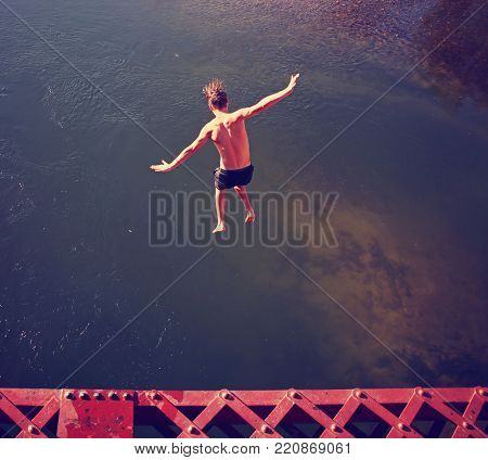 a boy jumping of an old train trestle bridge into a river toned with a retro vintage action on a hot summer day