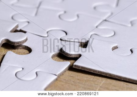 close up of white jigsaw/puzzle with a row in wrong position, over  wooden table background, symbol of problem solving and new vision