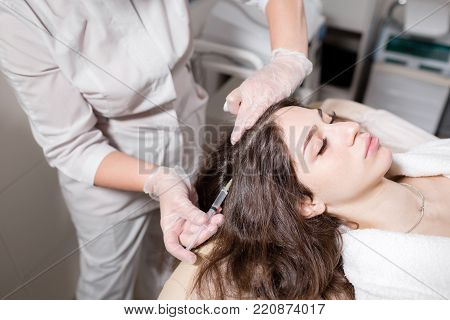Handsome woman receives an injection in the head. The procedure makes doctor in white gloves. The concept of mesotherapy. Thrust to strengthen the hair and their growth.