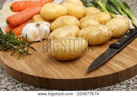 raw potato, fresh spring onion, carrot and garlic with kitchen knife on a wooden board