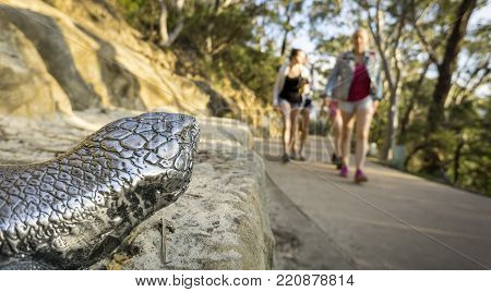Sydney, Australia - Apr 18, 2017: Metal lizard figure placed along Three Sisters Footpath overlooking some blurred out recreational walkers. At Echo Point, Katoomba, Blue Mountains National Park.