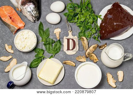 Food is source of vitamin D. Various natural food rich in vitamins. Useful food for health and balanced diet. Prevention of avitaminosis. Small cutting board with name of vitamin D. Top view