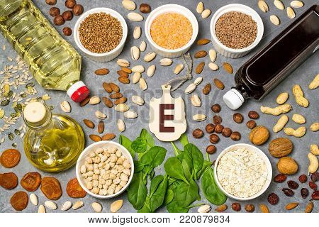 Food is source of vitamin E. Various natural food rich in vitamins. Useful food for health and balanced diet. Prevention of avitaminosis. Small cutting board with name of vitamin E. Top view