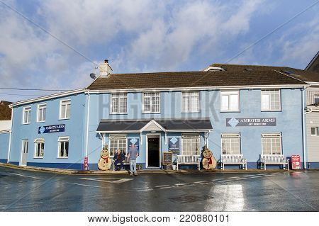 Amroth, Wales, UK: January 01, 2018: The Amroth Arms Hotel is a popular pub and restaurant with locals and tourists alike. Two men talk outside the door.