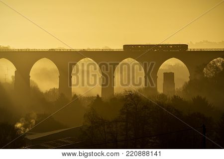 Misty Sunrise With Moorswater Viaduct And Train Passing Over