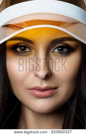 Closeup portrait of beautiful adult woman wearing yellow visor.