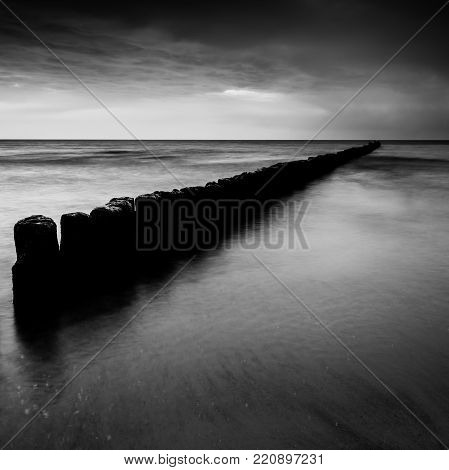 sunset over the sea with a wooden pier, black and white photo, long exposure