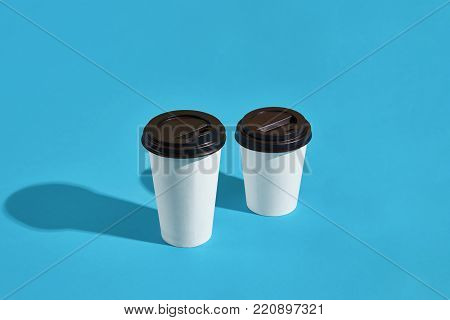 Flat lay design of 2 hot coffee cups on blue background with copy space. Still life. Two white paper cups with black lids