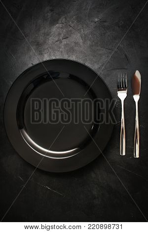 single plate and flatware on black background. Sophisticated and simple crockery. Dinner for one and loneliness concept poster