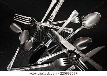 Silver cutlery on black background. Dishes cleaning after a party concept