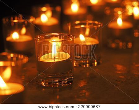 Glass candle light with shallow depth of field. Christmas golden candles light burning of candle flame at night.