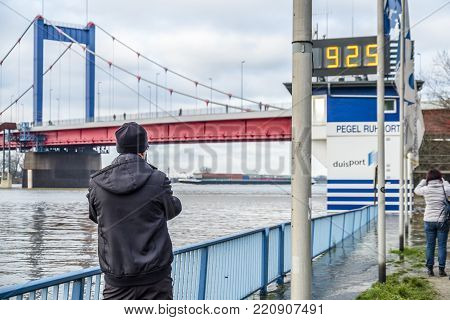 DUISBURG , GERMANY - JANUARY 08 2017 : Tourist observing the the river Rhine flooding the promenade in Ruhrort