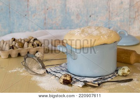 A special yeast dough for making homemade pies and buns in a small saucepan, next to quail eggs and a sieve for sifting the flour. Selective focus.