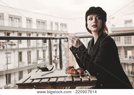 Portrait of young businesswoman sitting near a table in breakfast time. Self-employment concept