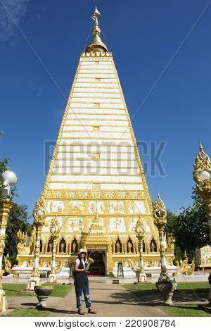 Asian Thai Woman Praying Buddha And Chedi At Wat Phra That Nong Bua In Ubon Ratchathani, Thailand