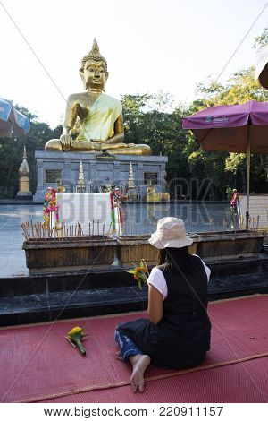 Thai woman respect praying and visit Golden big buddha statue name Phra Mongkol Ming Muang at Buddha garden on September 18, 2017 in Amnat Charoen, Thailand