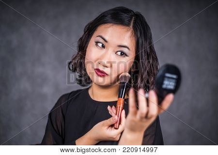 pretty asian woman in black dress on gray background making up