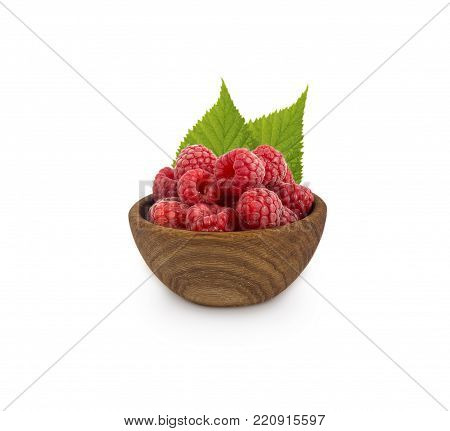 Raspberries in a wooden bowl isolated on white background. Raspberry with leaves close-up. Vegetarian or healthy eating. Juicy and delicious raspberries.