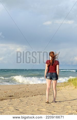 back of redhead woman on beach after a storm
