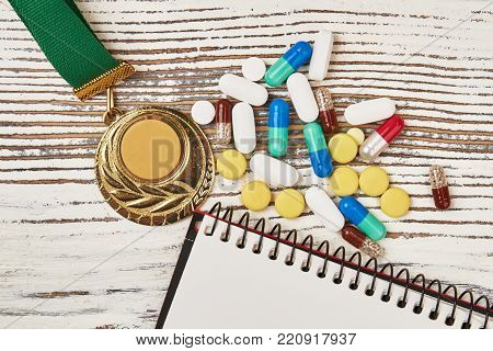 Golden medal and heap of banned drugs on wooden background. Tablets and capsules. Deception and cheating in sport.