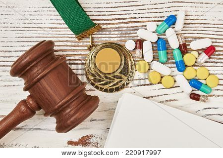 Judicial hammer, medal and pills on wooden table. Steroids and stimulants. Crime in sports, scandals and trials.