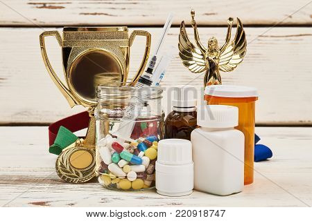 Trophies and diverse medicaments. Reaching victory by unfair play. Doping scandals and sport.