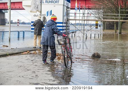 DUISBURG , GERMANY - JANUARY 08 2017 : Lady surprised by the river Rhine flooding the promenade in Ruhrort