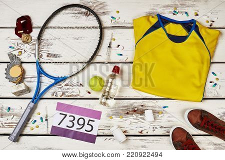 Tennis player's uniform and racquet on wooden table. Using banned drugs to win competition. Unfairly earned trophy and medals.